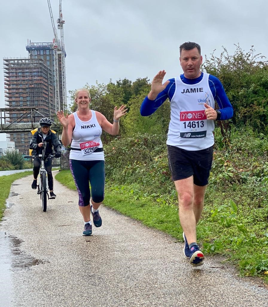 Nikki and Jamie running their London Marathon. There are buildings under construction in the distant background. They followed by a friend on her bicycle.