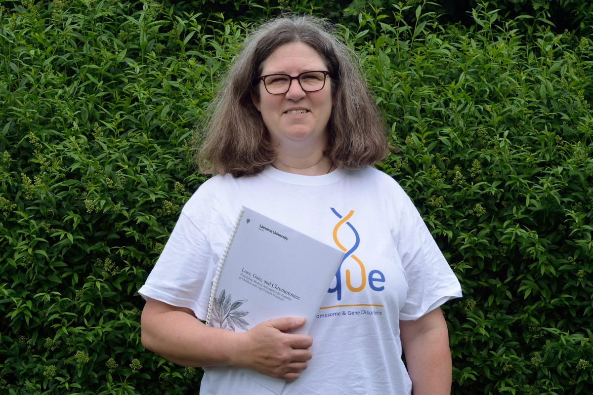 Photo shows Kristina wearing a Unique tshirt and holding her thesis